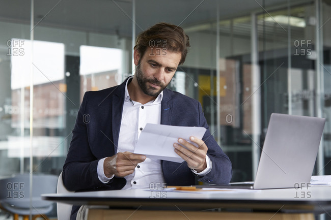 Businessman examining document while sitting in office