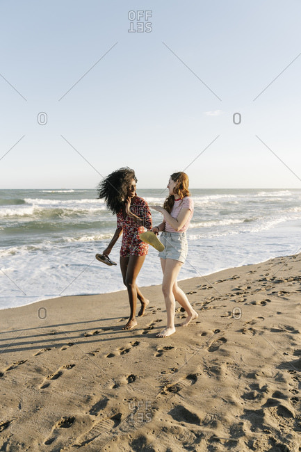 Young friends enjoying while walking on beach during sunny day