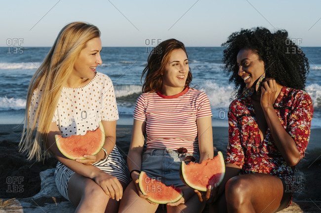 Friends spending time while eating watermelon on beach
