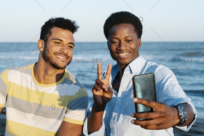 Smiling friends taking selfie on smart phone at beach during sunny day