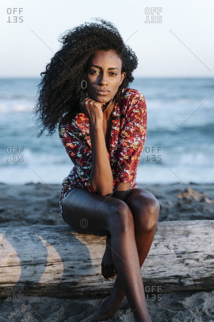 Young woman with hand on chin sitting at beach during sunny day