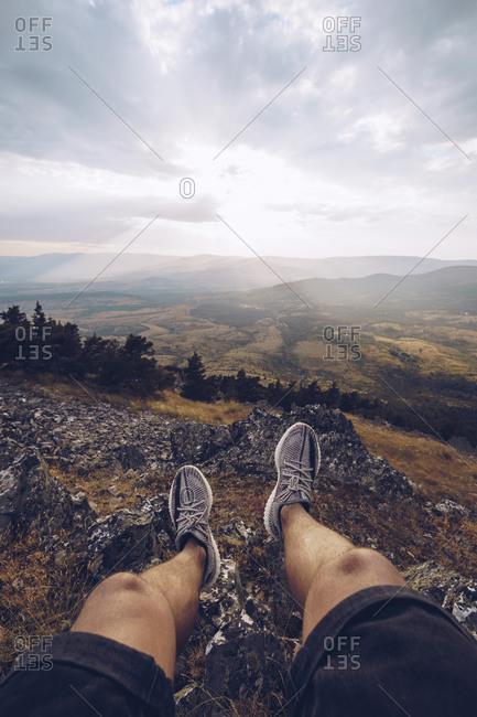 Legs of man sitting on rocks in Puerto de la Puebla mountain pass at sunset