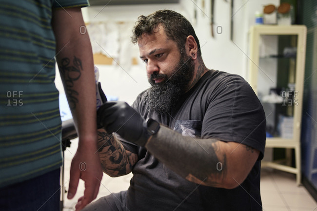Bearded male artist tattooing on man's hand in studio
