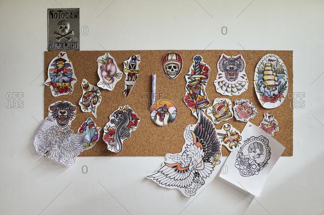 Tattoo designs hanging on bulletin board in studio