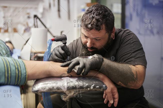 Bearded artist tattooing on male customer's hand in studio