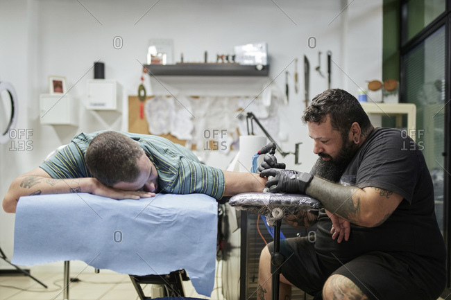 Male artist tattooing on customer's hand in studio