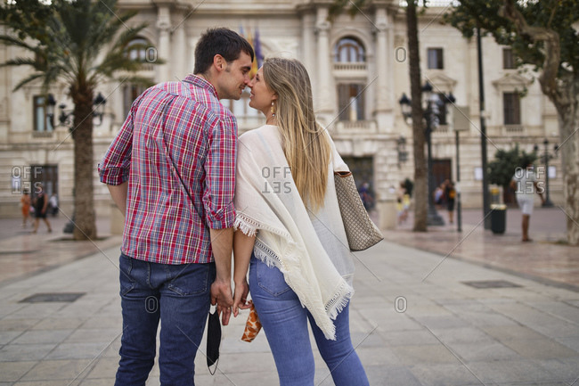 Couple nuzzling nose while standing in city