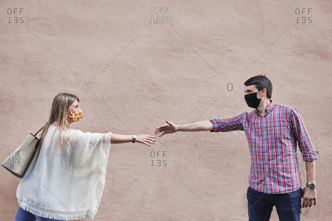 Couple keeping social distance while standing against wall