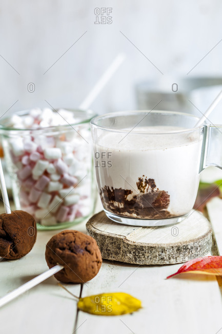 Close-up of hot chocolate with marshmallows and truffle lollipops on table at home