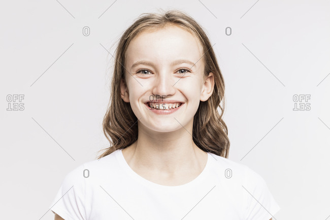 Close-up of cute smiling girl against white background