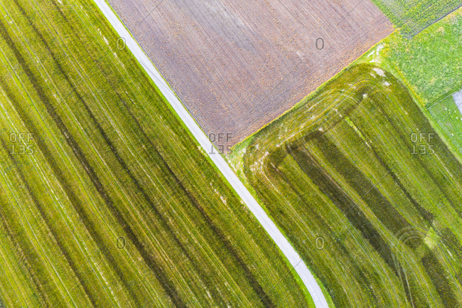 Drone view of dirt road stretching between green countryside fields