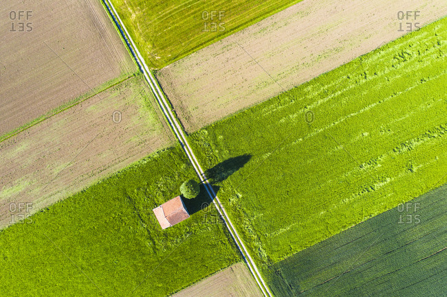 Drone view of dirt road stretching between countryside fields in spring