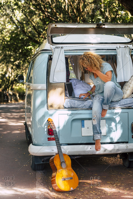 Mature woman using laptop while sitting on bed of motor home