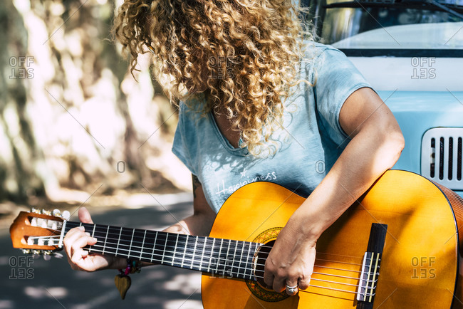Mature woman with curly hair playing guitar while leaning on motor home