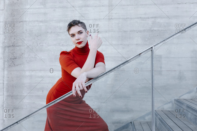 Confident trans man wearing red dress standing on steps against wall