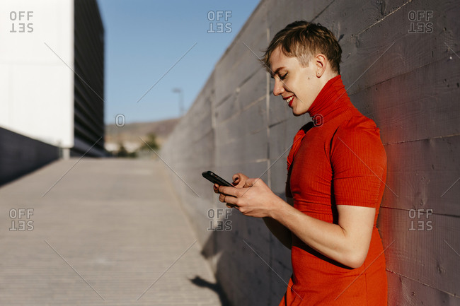 Non-binary man text messaging on smart phone while standing against wall