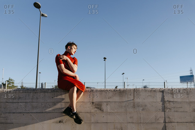 Non-binary man sitting on surrounding wall against clear sky