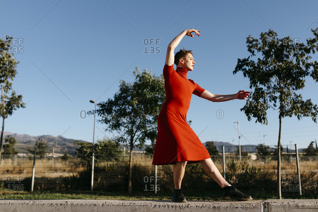 Non-binary male wearing red dress dancing on retaining wall