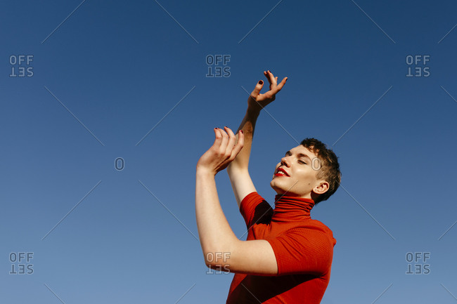 Gender fluid man dancing against clear sky on sunny day