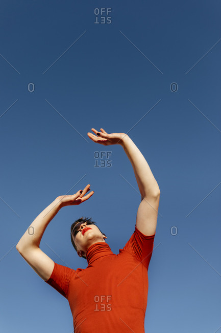 Non-binary male with hand raised standing against clear sky on sunny day