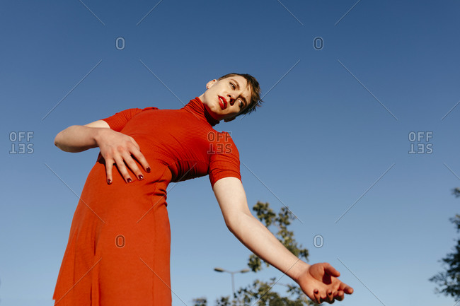Non-binary male dancing against clear sky on sunny day