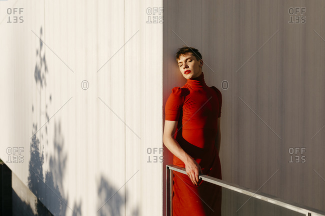 Gender fluid man standing against wall during sunset