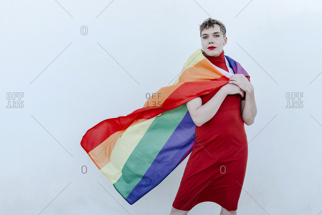 Non-binary person wearing rainbow flag around neck while standing against white background