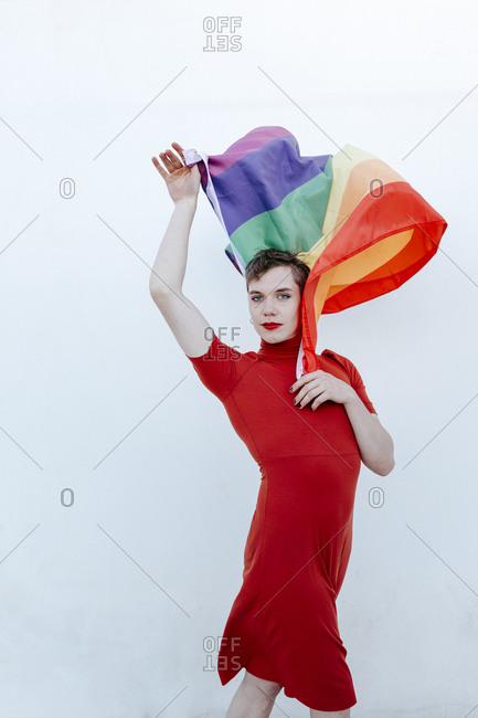 Non-Binary person waving rainbow flag while standing against white background
