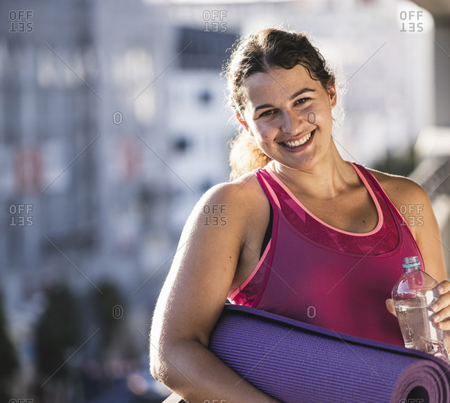 Smiling woman holding exercise mat and water bottle while standing on terrace