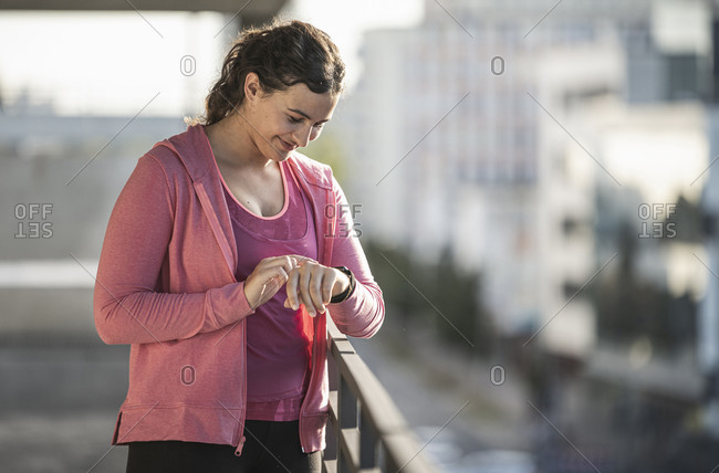 Smiling young woman checking time while standing by railing during sunny day