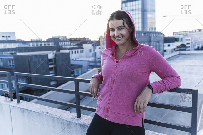 Smiling young woman wearing hood leaning on railing of terrace in city