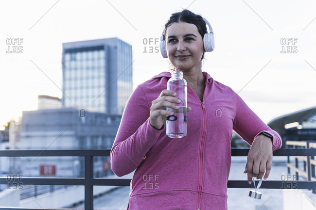 Young woman holding water bottle listening music over headphones on terrace at sunset