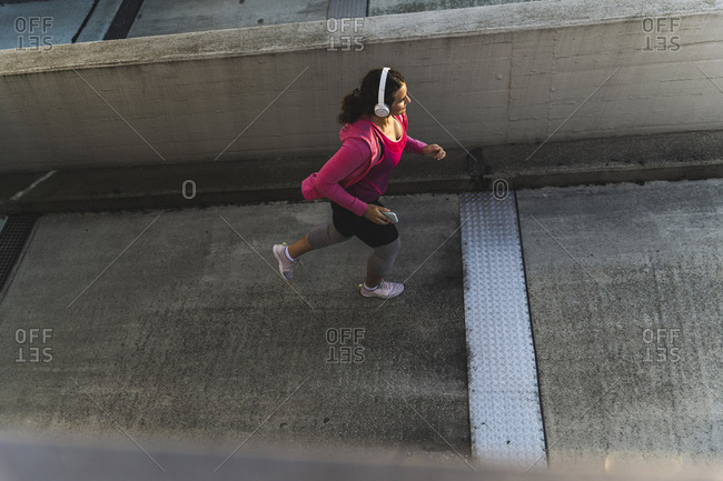 Young woman listening music while jogging on terrace at sunset