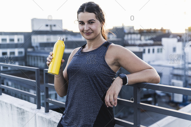 Smiling female athlete holding bottle while standing by railing on terrace
