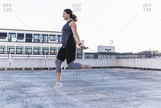 Young women exercising with jump rope on terrace against clear sky during sunset