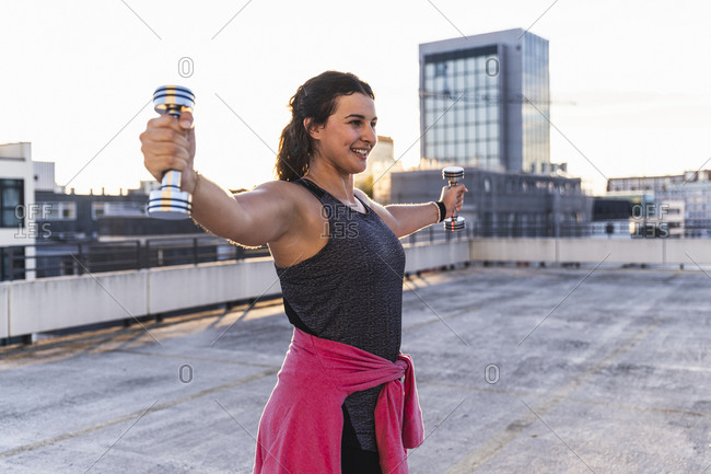 Smiling young woman with arms outstretched lifting dumbbells on terrace at sunset