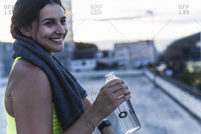Close-up of smiling young woman holding water bottle looking away while sitting on terrace
