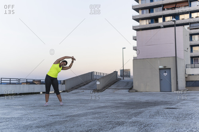 Female athlete with arms raised exercising on building terrace against clear sky