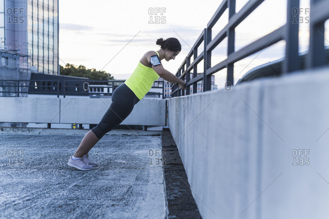 Young woman with arm band exercising on railing at sunset