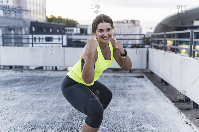 Smiling young woman boxing on terrace at sunset