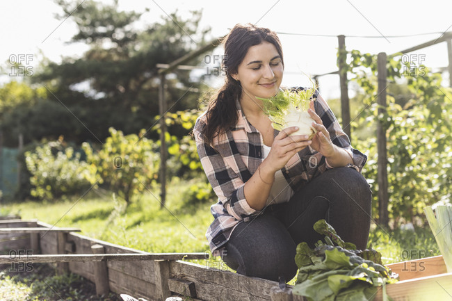 Smiling young woman with eyes closed smelling vegetable while crouching in garden