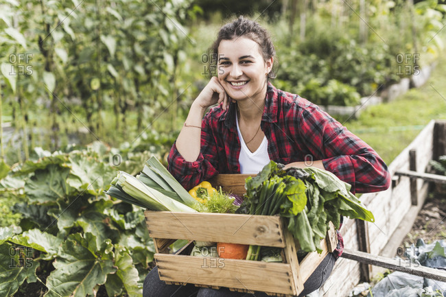 Smiling young woman sitting with vegetables in wooden crate at community garden