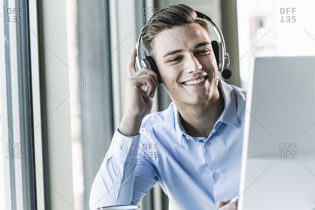 Close-up of smiling male customer representative talking over headset in office