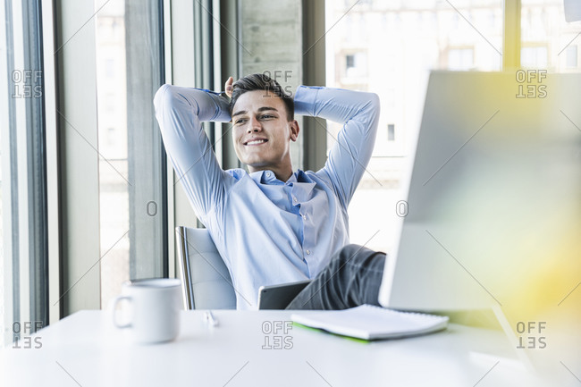 Thoughtful male professional with hands behind head sitting at desk in office