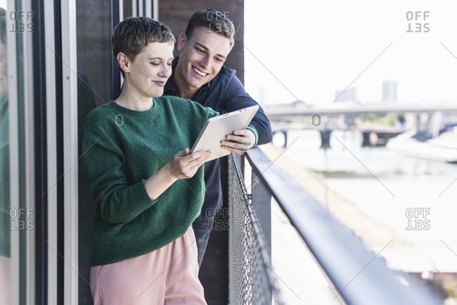 Smiling colleagues discussing over digital tablet while standing in balcony at office