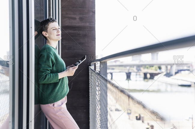Businesswoman with eyes closed holding digital tablet while standing in balcony