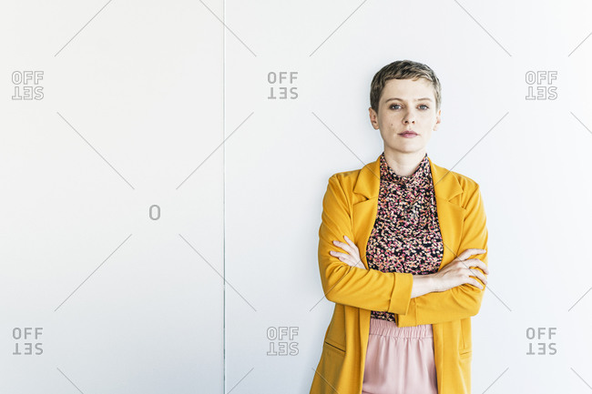 Confident businesswoman wearing yellow blazer standing against white wall in office