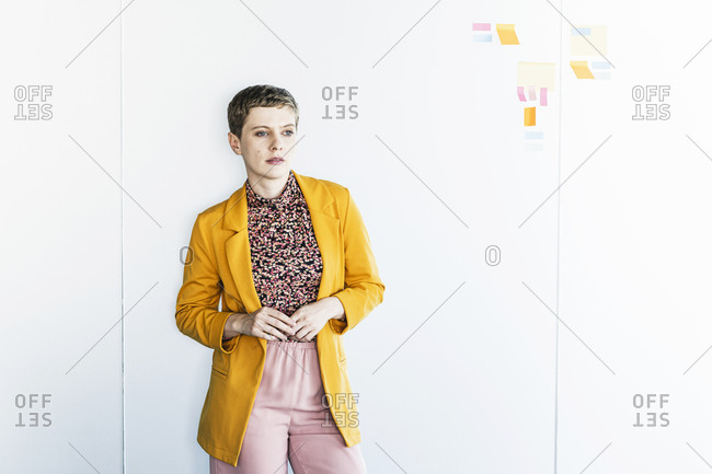 Thoughtful businesswoman wearing blazer standing against white wall in office