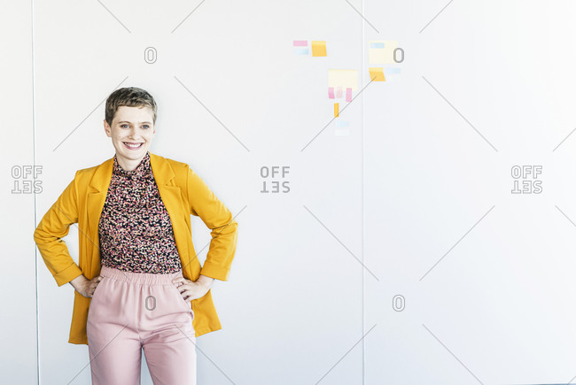 Smiling female entrepreneur with hands in pockets standing against white wall at office