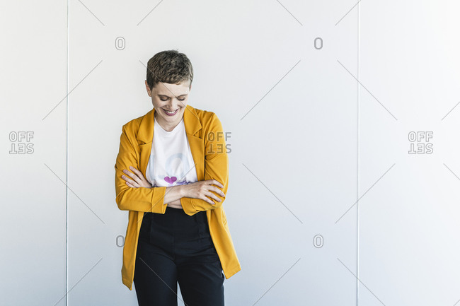Smiling businesswoman wearing yellow blazer with arms crossed standing against wall in office